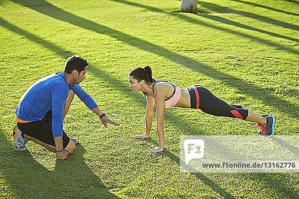 Persönlicher Trainer mit Frau bei einer Plankenübung