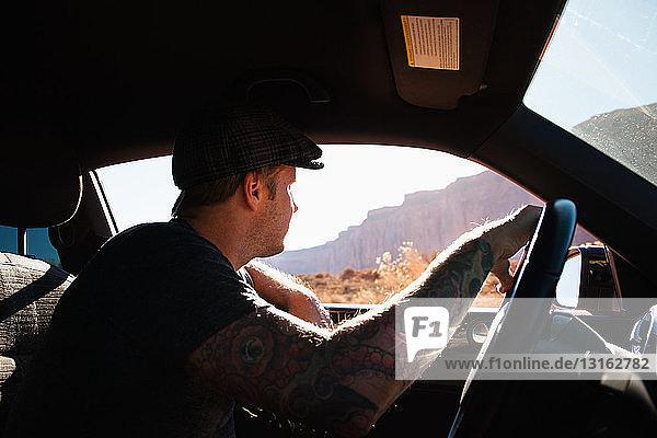 Mann fährt auf Autoreise  Monument Valley  Utah  USA