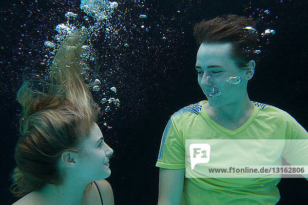 Young couple fully clothed floating underwater