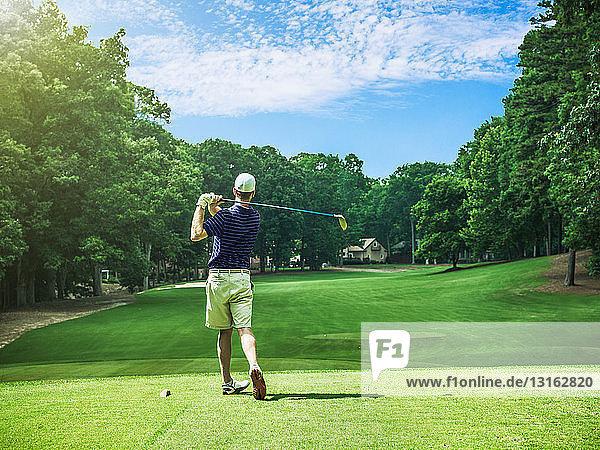 Rückansicht eines jungen männlichen Golfspielers beim Abschlag auf einem Golfplatz  Apex  North Carolina  USA