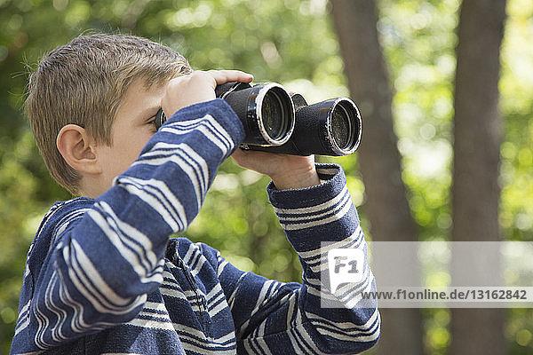 Junge schaut durch ein Fernglas im Wald