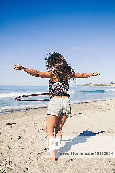 Frau mit Hula-Hoop-Reifen am Strand  Rückansicht