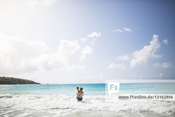 Mother standing in sea  carrying daughter