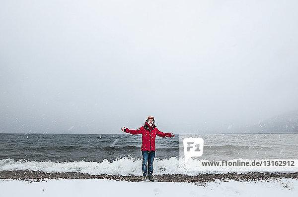 Vorderansicht eines jungen Mannes in rotem Mantel in voller Länge  der im Meer paddelt