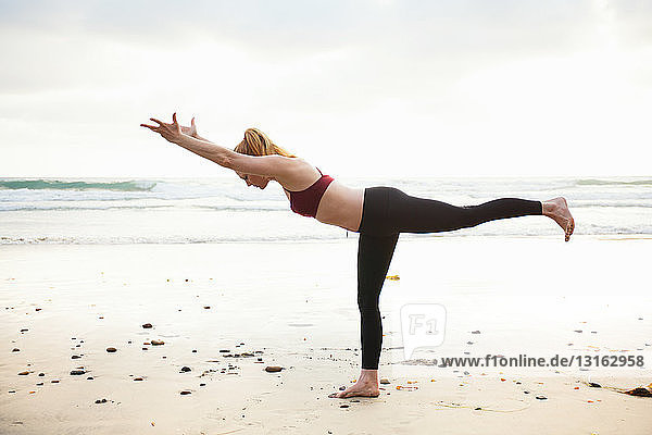 Mid adult woman practicing warrior yoga pose on beach
