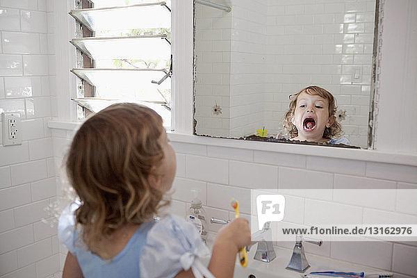 Weibliches Kleinkind schaut beim Zähneputzen in den Spiegel