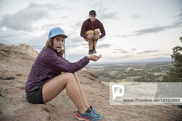Junger Mann springt in der Luft auf die Hand einer jungen Frau  Smith Rock  Oregon  USA