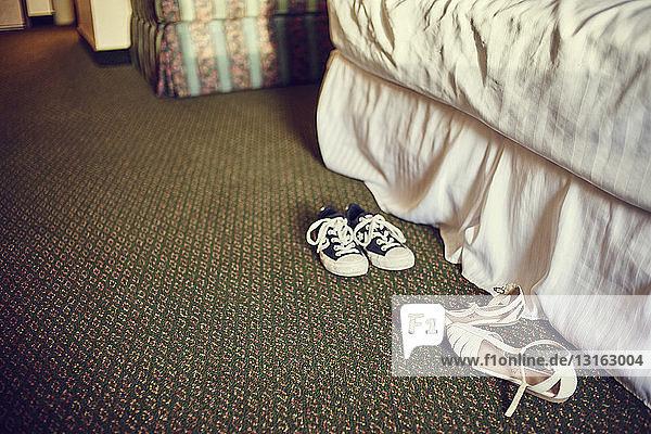 Paar Turnschuhe und Sandalen auf Schlafzimmerteppich