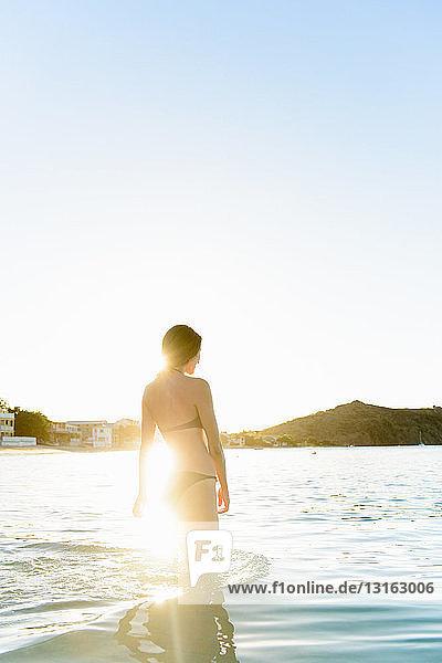 Woman walking in water on beach