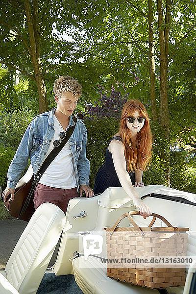 Junges Paar stellt Picknickkorb auf den Rücksitz eines Oldtimer-Cabrios