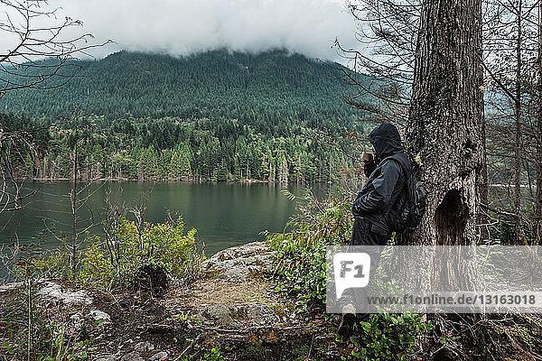 Man wearing waterproof clothes by tree  Buntzen Lake  British Columbia  Canada