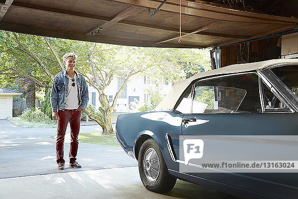 Young man staring into garage at vintage car