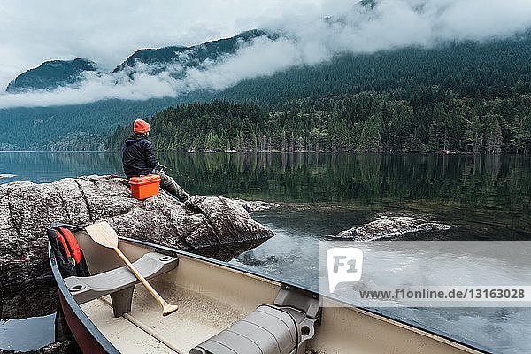 Man fishing from rocks  Buntzen Lake  British Columbia  Canada