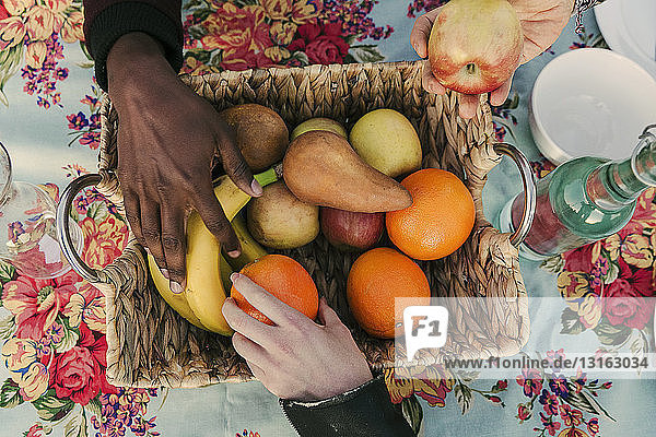 Three adult hands selecting fruit form basket