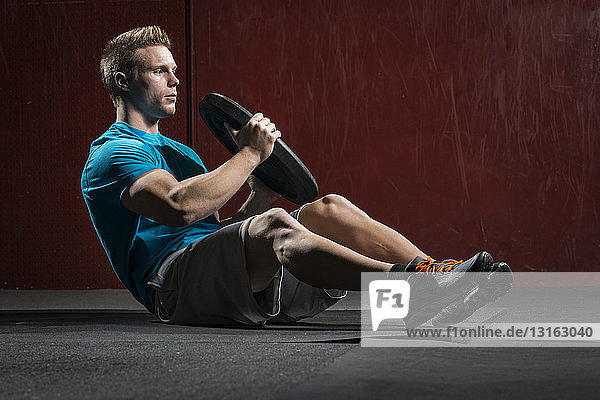 Man holding weight plate doing sit ups