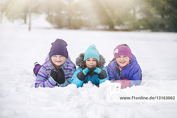 Freunde mit Strickmützen liegen nebeneinander im Schnee auf der Vorderseite und schauen lächelnd in die Kamera