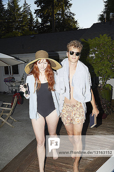 Young couple wearing swimwear strolling on poolside at dusk