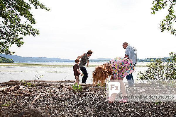 Mädchen und Familie werfen Steine in den Fluss