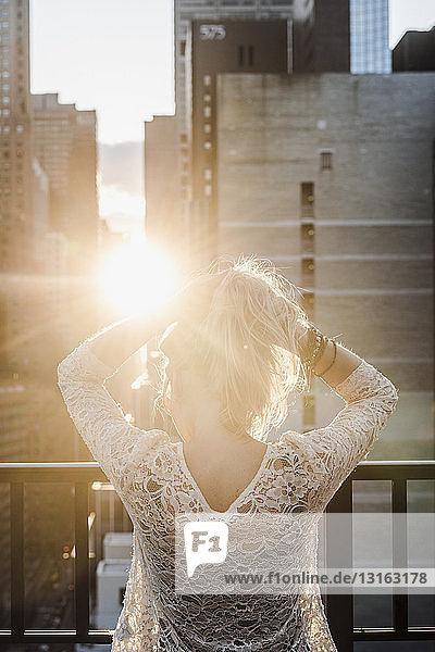 Junge Frau mit Händen im Haar im Sonnenlicht