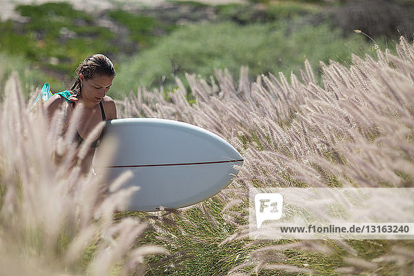 Young woman walking through tall grass carrying surfboard looking down