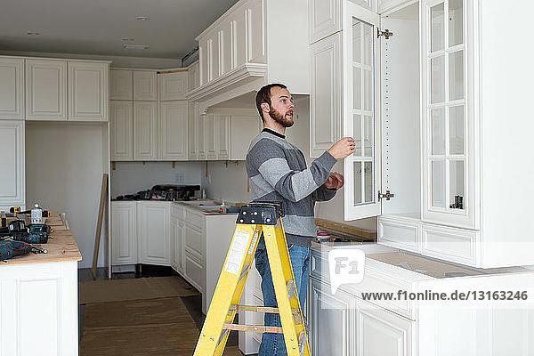 Schreiner beim Einbau des Küchenschranks