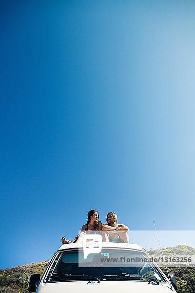 Paar entspannt  auf dem Dach eines Wohnmobils sitzend