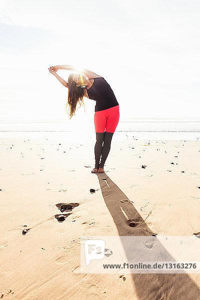 Frau in Yoga-Pose am Strand