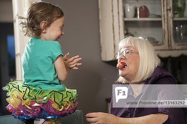 Mädchen füttert Großmutter mit einer Erdbeere