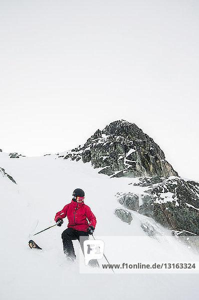 Frontansicht eines jungen Mannes beim Skifahren auf einem schneebedeckten Berg  Whistler Blackcomb Skigebiet  Britisch-Kolumbien  Kanada