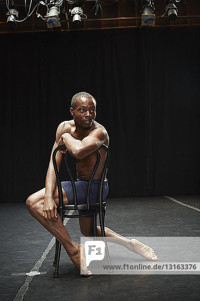 Dancer sitting back to front on chair