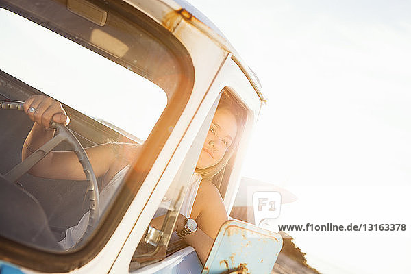 Young female surfer looking out from pickup truck window