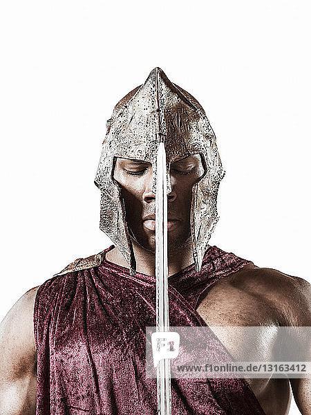 Studioporträt eines souveränen jungen Mannes als Gladiator verkleidet mit Helm und Schwert