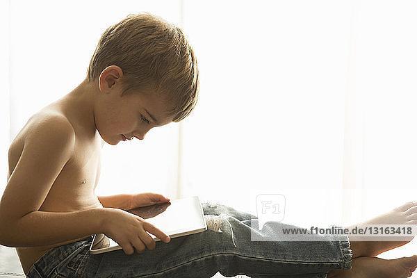 Junge benutzt digitales Tablett zu Hause