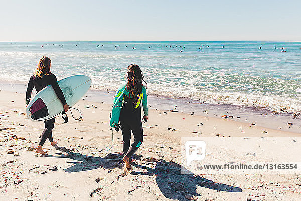 Paar mit Surfbrettern in der Hand  auf das Meer hinausgehend  Rückansicht