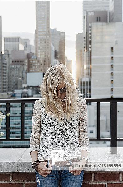 Junge Frau mit Stadtansicht im Hintergrund