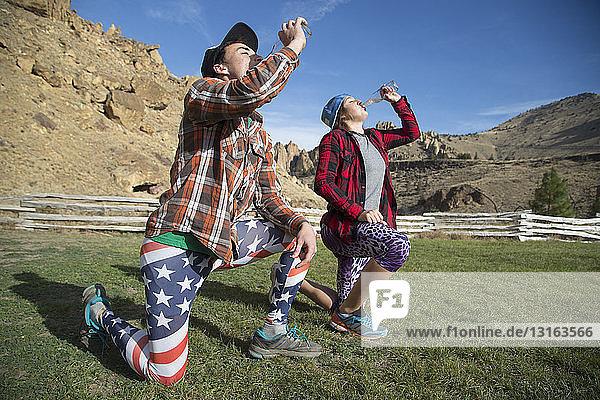 Freunde knien und trinken  Smith Rock State Park  Oregon  USA