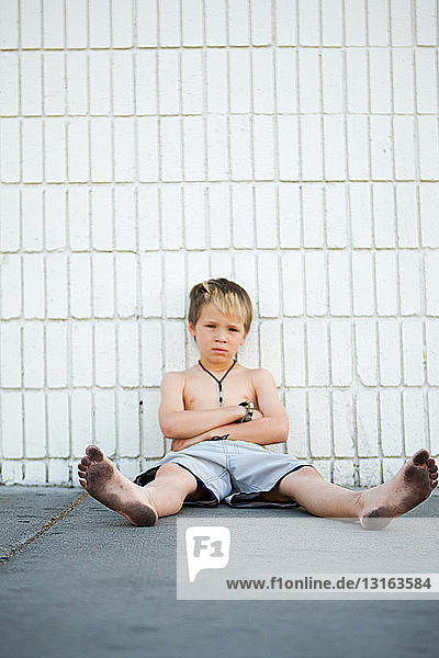 Boy with dirty feet sitting by brick wall