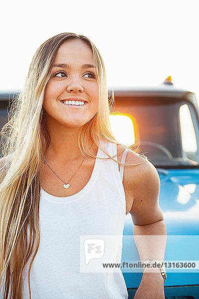 Porträt einer jungen Frau  die sich an einen Pickup lehnt