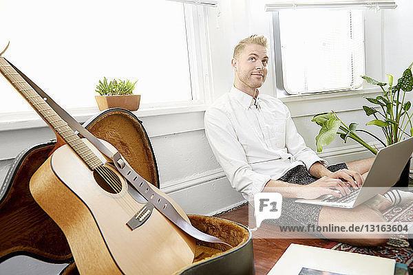 Mann sitzt auf dem Boden vor dem Fenster mit Laptop und schaut weg