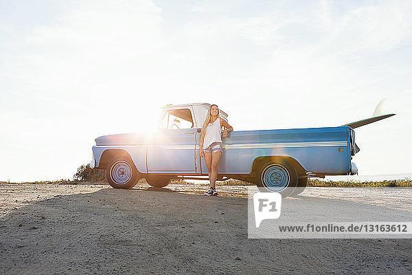 Porträt einer jungen Surferin  die sich am Strand an einen Pickup lehnt  Encinitas  Kalifornien  USA