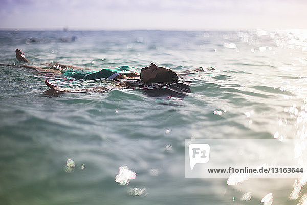 Frau schwimmt auf dem Rücken im Meer