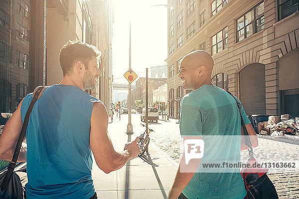 Zwei männliche Freunde unterhalten sich nach der Rückkehr vom Training