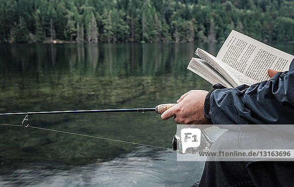 Man fishing with book  Buntzen Lake  British Columbia  Canada