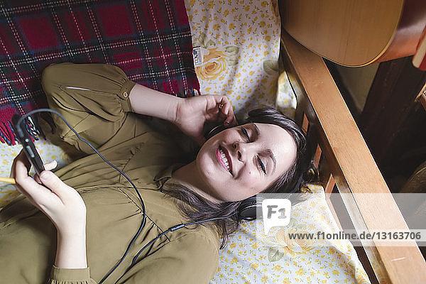 Junge Frau liegt auf Sofa und hört Musik Junge Frau liegt auf Sofa und hört Musik