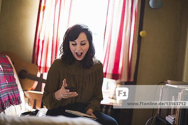 Junge Frau mit offenem Mund und Blick auf Smartphone Junge Frau mit offenem Mund und Blick auf Smartphone