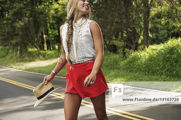 Junge Frau mit Hut über die Straße