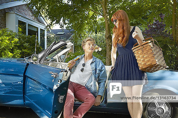 Young couple with vintage convertible holding picnic basket