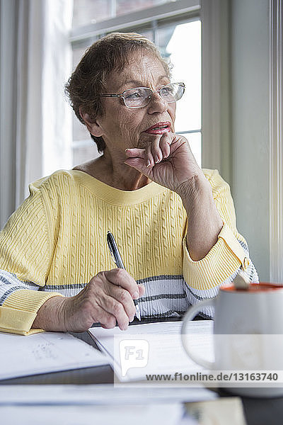 Ältere Frau denkt am Schreibtisch