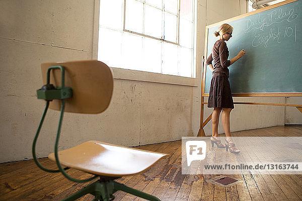 Lehrerin schreibt auf Tafel mit leerem Stuhl im Vordergrund