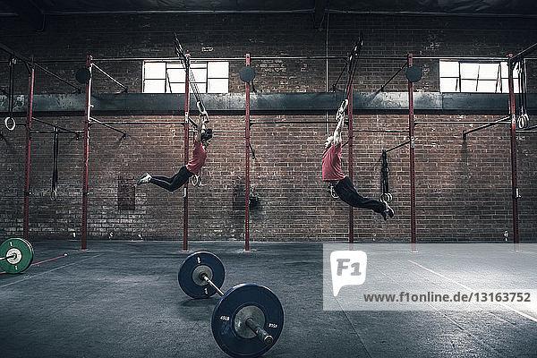 Junge Männer und Frauen schwingen auf Turnringen im Fitnessstudio